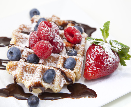 Belgian waffle with powdered sugar, chocolate syrup, and fruit on white