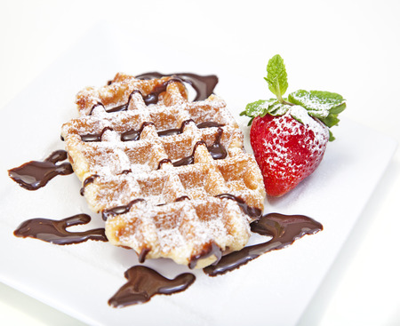 Belgian waffle with powdered sugar and chocolate syrup
