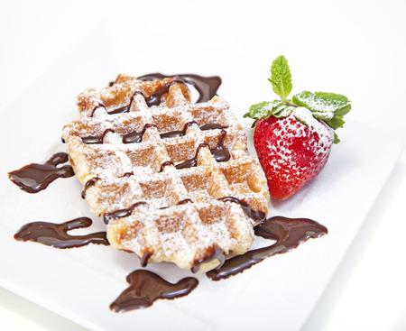 waffles: Gofre belga con azúcar en polvo y el jarabe de chocolate