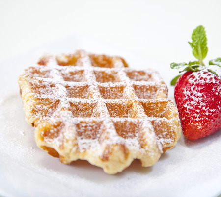 Belgian waffle with powedered sugar and a strawberry