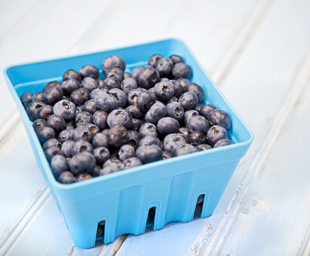 Container of blueberries on a blue wooden table Stock Photo