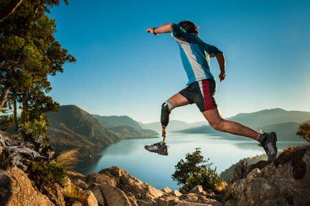 Gehandicapte mens met beenprothese, springen in Patagonië