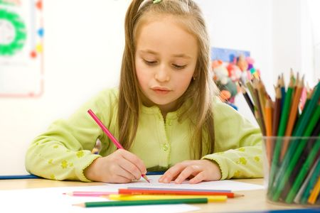 Pretty girl sitting and drawing with colored pencils Stock Photo - 2312500