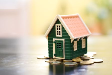 Miniature green house on coins base Stockfoto