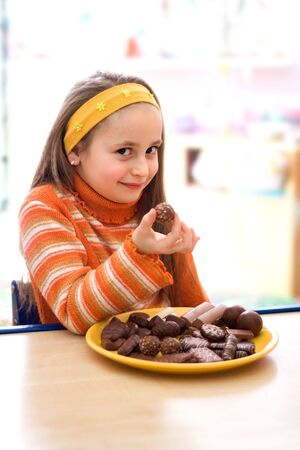 Pretty young girl taking a peace of chocolate from tray Stockfoto