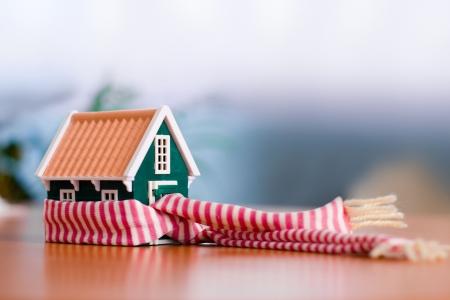 warm colors: Bufanda alrededor de una casa verde en miniatura - conceptual fin de proteger o aislar a casa