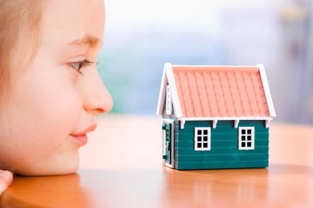 miniature people: Child dreaming about a new house or home Stock Photo