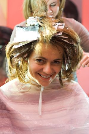 Happy woman sitting at the hair stylist, her hair is being bleached photo