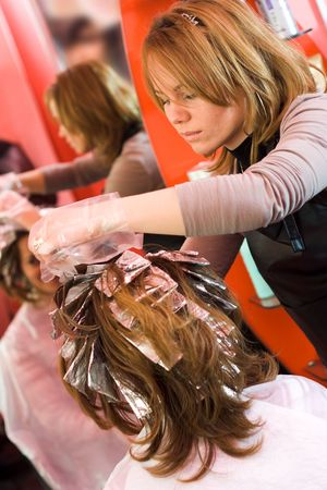 Woman's hair being painted at the hair stylist photo