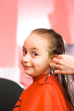 Pretty young girl's hair being arranged at the hair stylist Stock Photo - 2457353