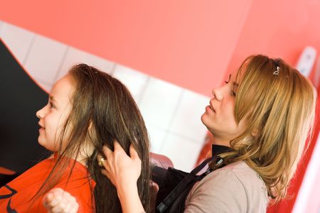 Child's hair being arranged at the hair stylist photo