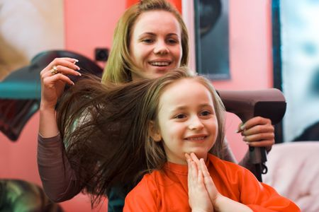Happy girl sitting at the hair stylist, shes hair is being dried Stock Photo - 2457356