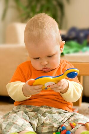 Baby boy sitting and playing - looking at a colorful plastic toy Stock Photo - 2564381