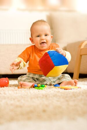 Baby boy sitting on the ground and playing with a colorful cube Stock Photo - 2564375