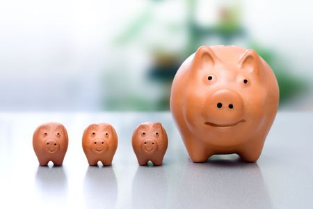 compounding: Conceptual view of compound interest - big piggy-bank and the small ones