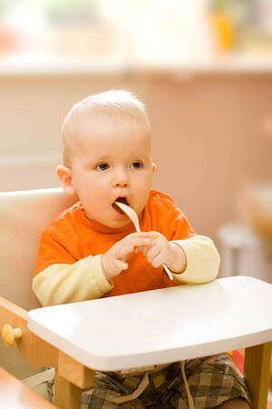 Little  boy playing with spoon after lunch Stock Photo - 3252561