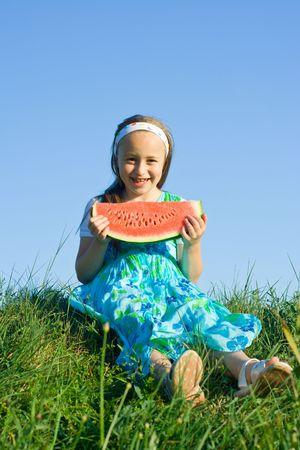 Happy little girl holding a fresh watermelon slice Stock Photo - 3260957