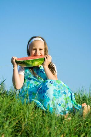 Little girl sitting at meadow and eating watermelon Stock Photo - 3260955