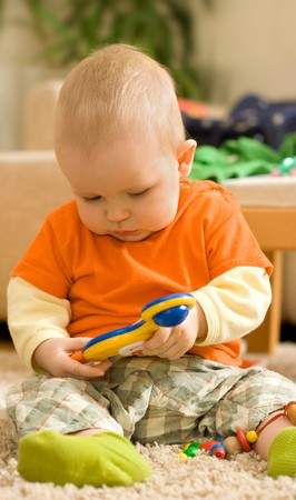 Baby boy sitting and playing - playing with a colorful plastic toy Stock Photo - 4291256