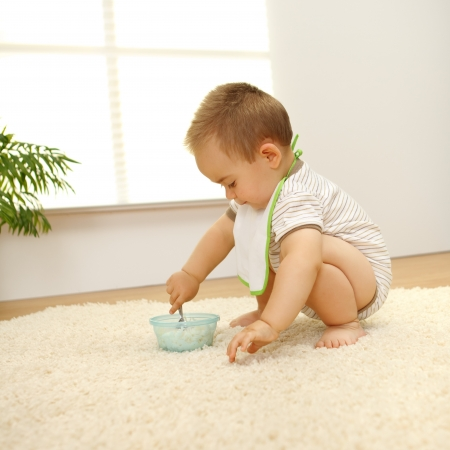 squat: Little baby boy eating alone on white carpet Stock Photo