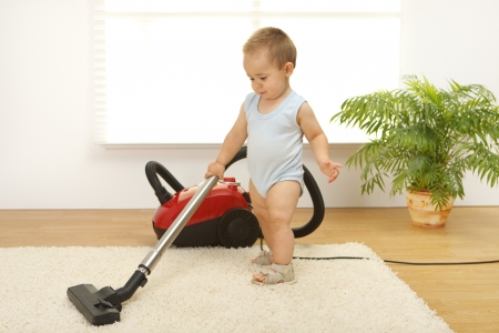 Baby boy cleaning the carpet with vacuum cleaner photo