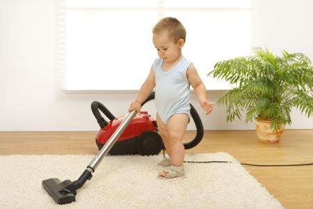 cleaners: Baby boy reiniging van het tapijt met stofzuiger