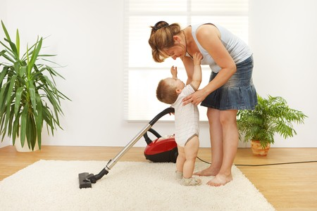 Mother trying to clean the floor while shes baby is crying and wants to be picked up Stock Photo