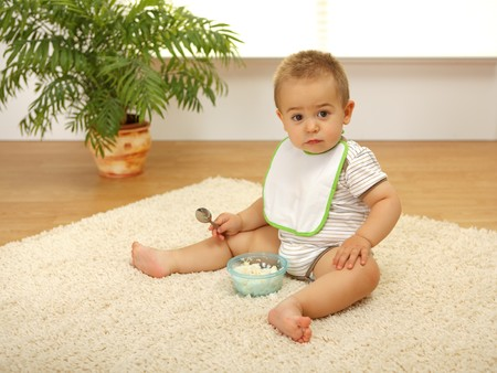Little baby boy sitting alone on white carpet and eating photo