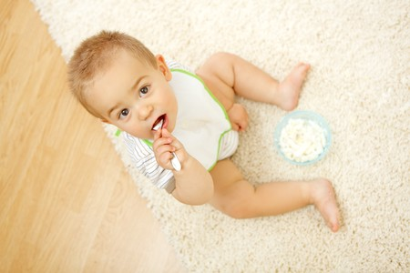 Little baby boy sitting alone on white carpet and eating Stock Photo - 7515578