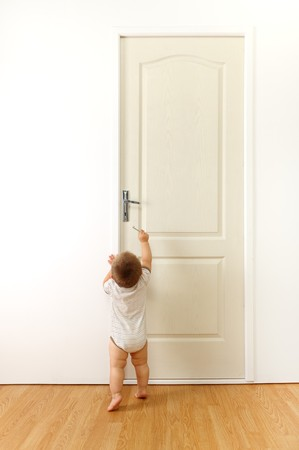 Baby in front of a closed door, trying to reach the keyhole with key
