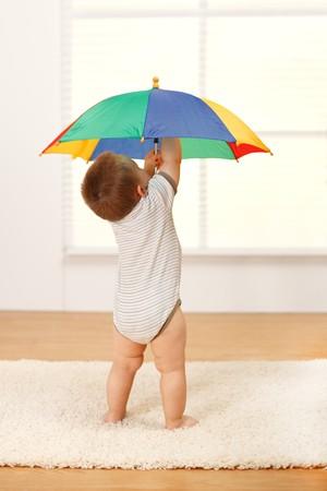 Kleine baby jongen openen een kleurrijke umbrella