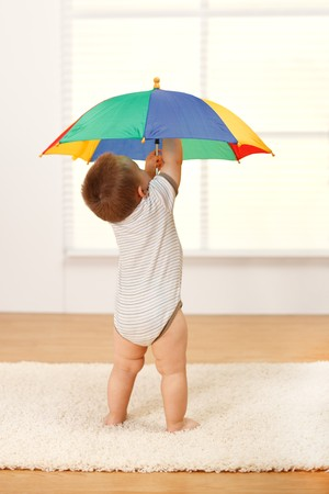 Little baby boy opening a colorful umbrella
