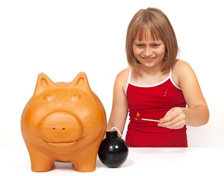 Little girl lighting a bomb to explode the piggy bank Stock Photo - 7515570