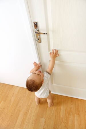wants: Baby boy crying, wants to reach the door handle. Conceptual view of being out of reach because of being too small for something