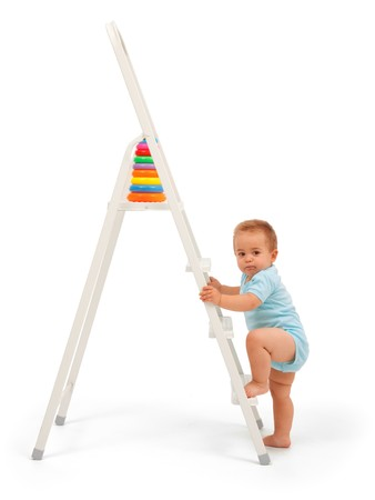 Serious baby boy wants to reach the target: walk up the ladder and get the toy