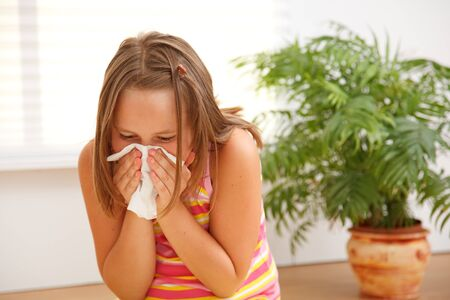 Teen girl blowing out her nose because of allergic reaction on plants photo