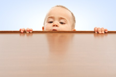 little table: Curious little boy climbing up and looking onto table surface