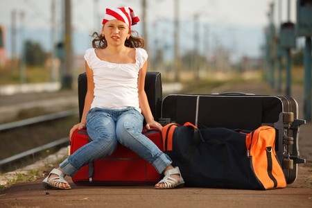 baggage train: Young girl sitting on luggage and waiting for train in the station