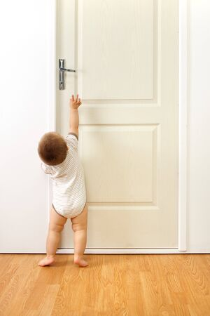 Baby boy in front of a closed door, trying to reach the handle Stockfoto