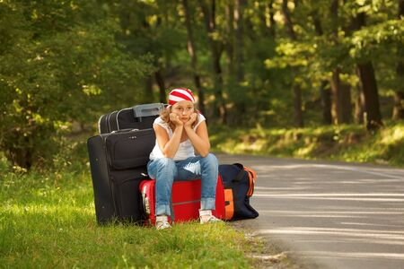 Young hitch-hiker girl standing on road side afternoon with bags Stock Photo - 7815436