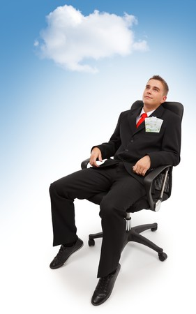 blue sky thinking: Young business man sitting in chair, under cloudy blue sky and dreaming about spending the money he has