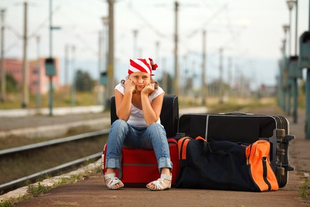delay: Young girl sitting on bag and waiting for train in the station Stock Photo