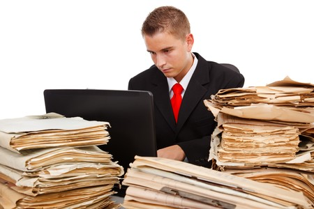 Man working on laptop computer, surrounded with lots of paperwork