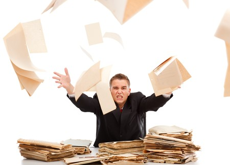 surrounded: Angry business man throwing away lots of paperwork