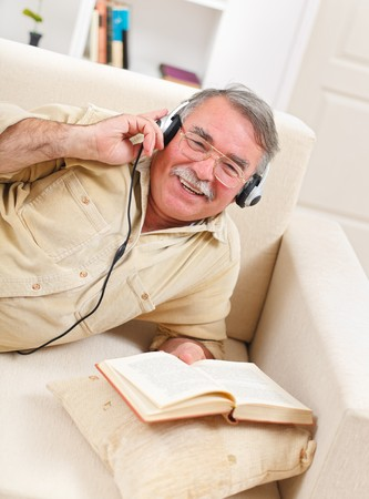 Happy senior man laying on sofa, reading and listening to music photo