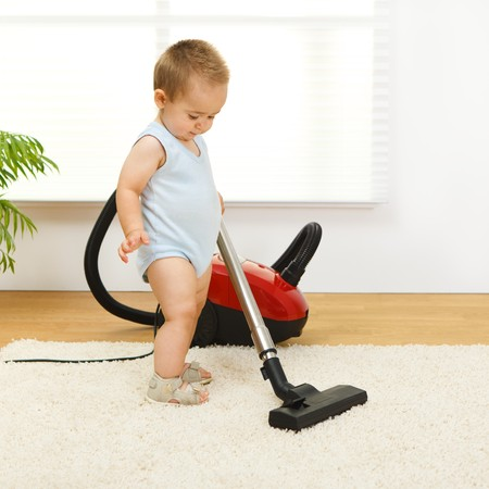 Baby boy cleaning the carpet with vacuum cleaner