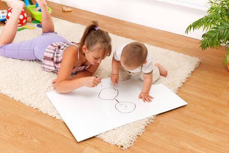 girl drawing: Brother watching his sister drawing on white sheet in the room