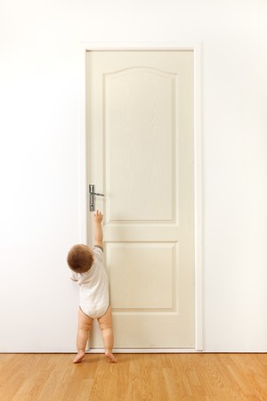 Baby in front of a closed door, trying to reach the handle