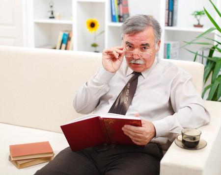 Senior man looking up while reading books in living room photo