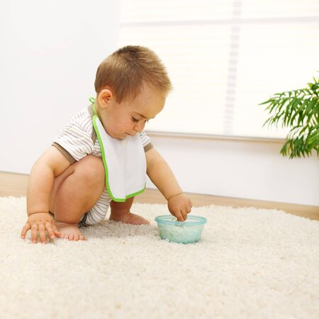 Little baby boy playing with food alone photo